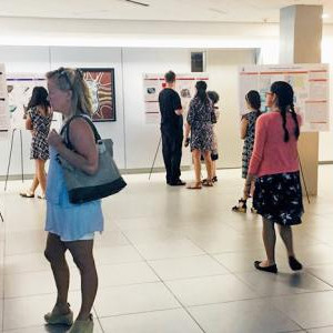 Multiple people browsing research posters in hallway